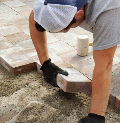 a worker laying a stone into place while constructing an interlock driveway