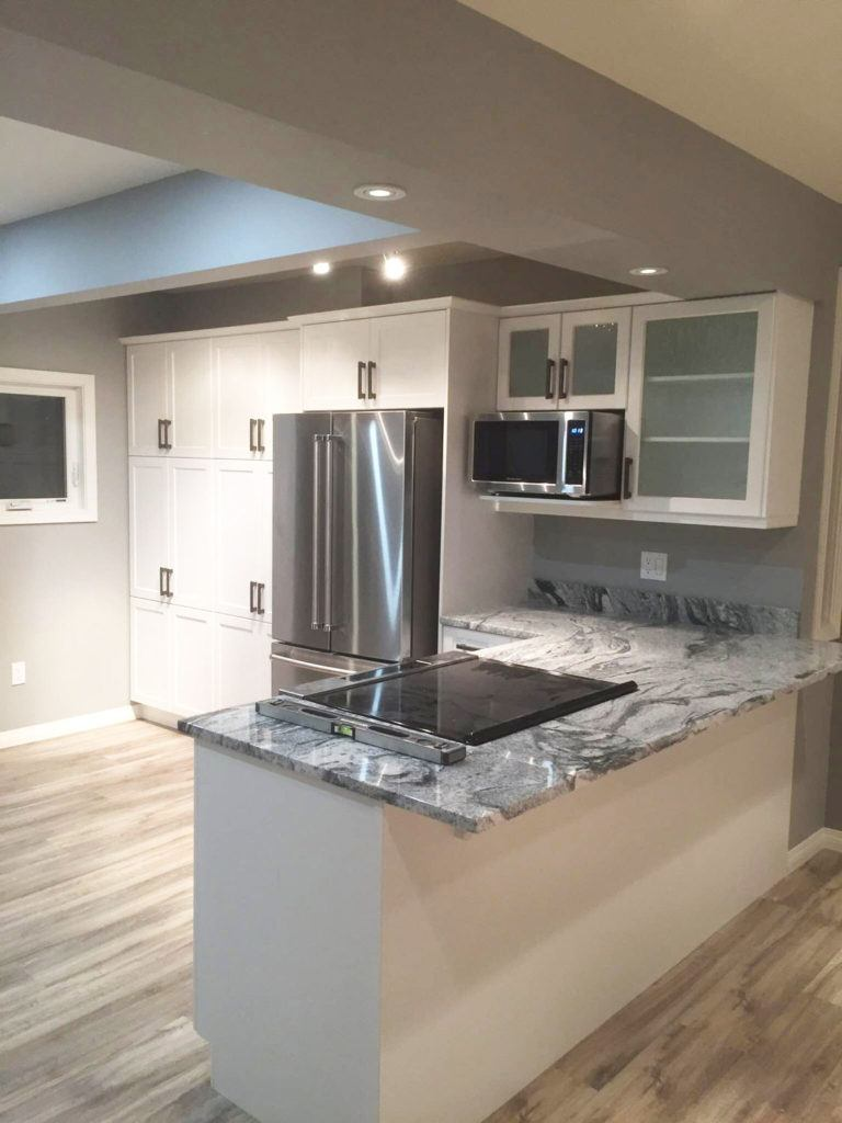 Custom kitchen renovation with stone countertop, white cabinets, and stainless steel appliances
