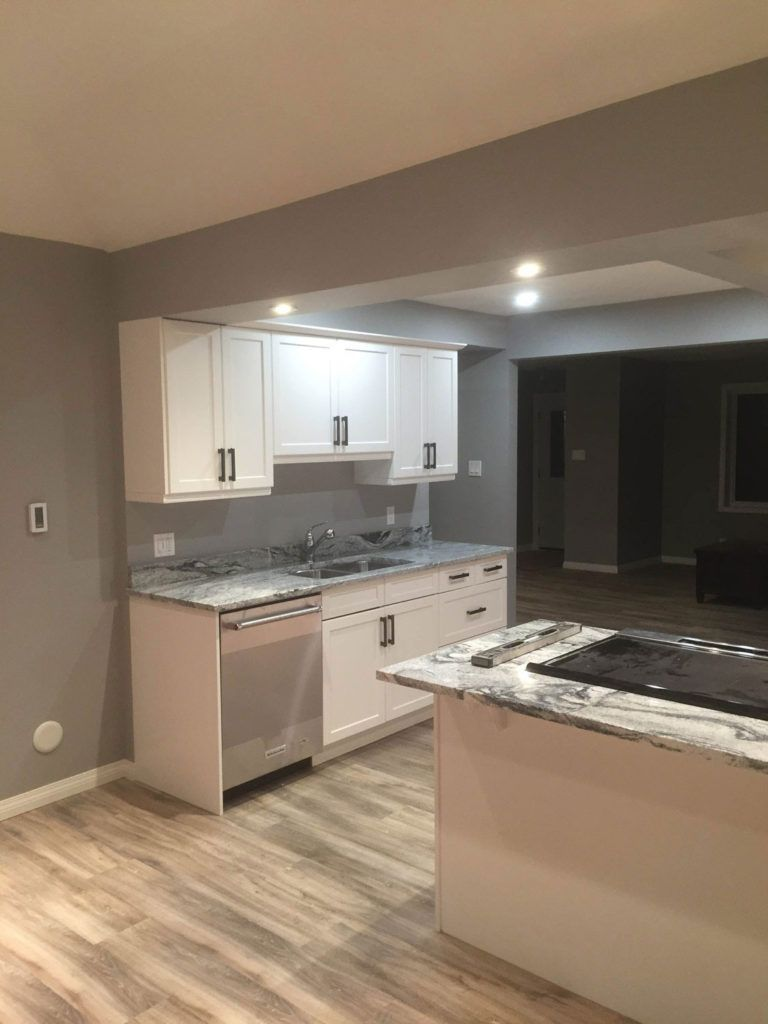 Custom renovated kitchen with white cabinets and wood floors