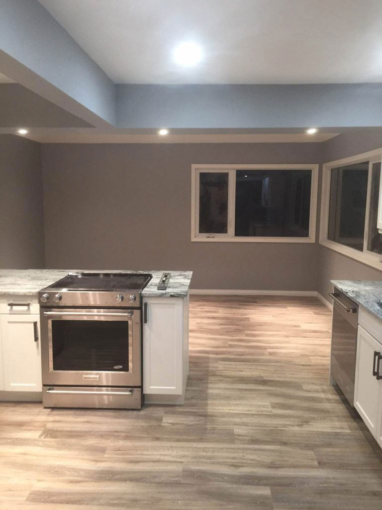 a newly renovated kitchen with stainless steel oven and dishwasher and wood floors