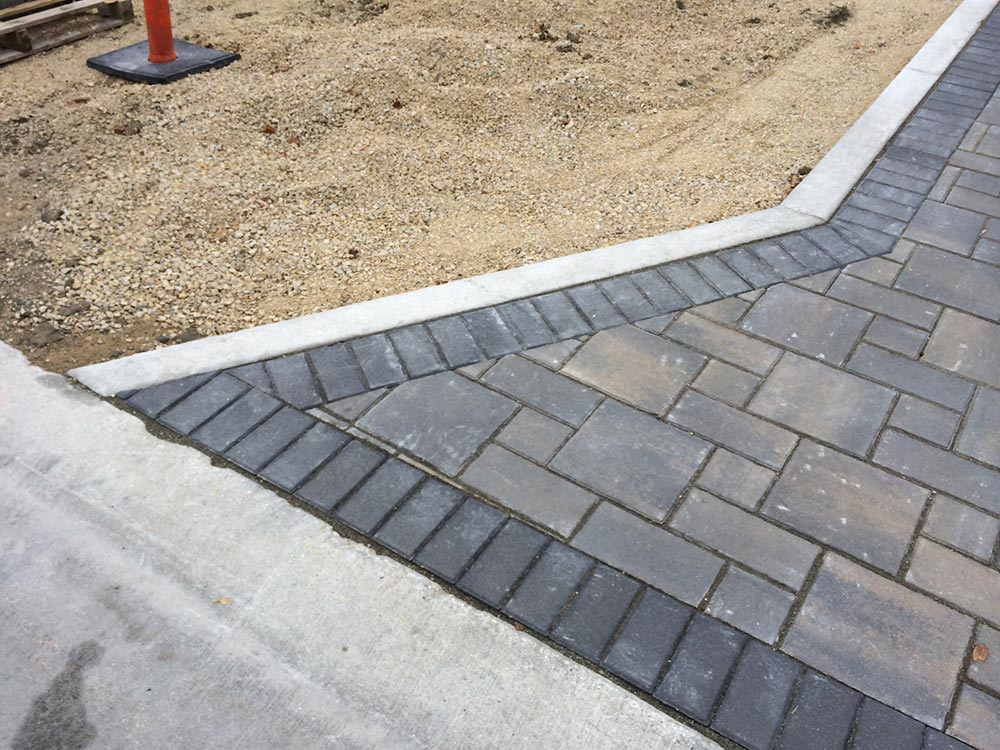 detailed edge of a stone interlock pathway outside of a new build house
