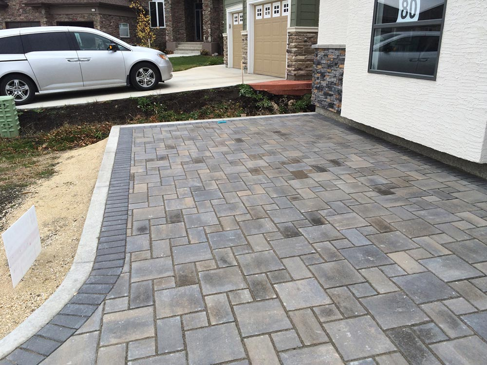 a stone interlock front patio in front of a stucco exterior new build house