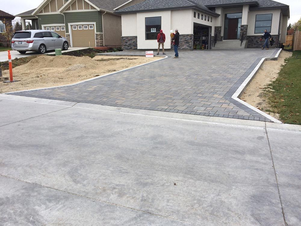 a new stone interlock driveway leading up to a residential home