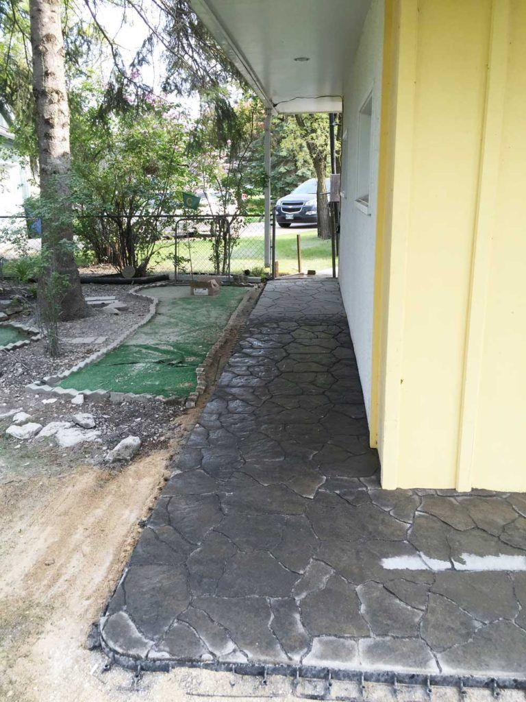 a flagstone walkway leading around the corner of a house