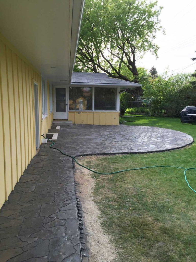 a large flagstone interlock backyard patio and walkway