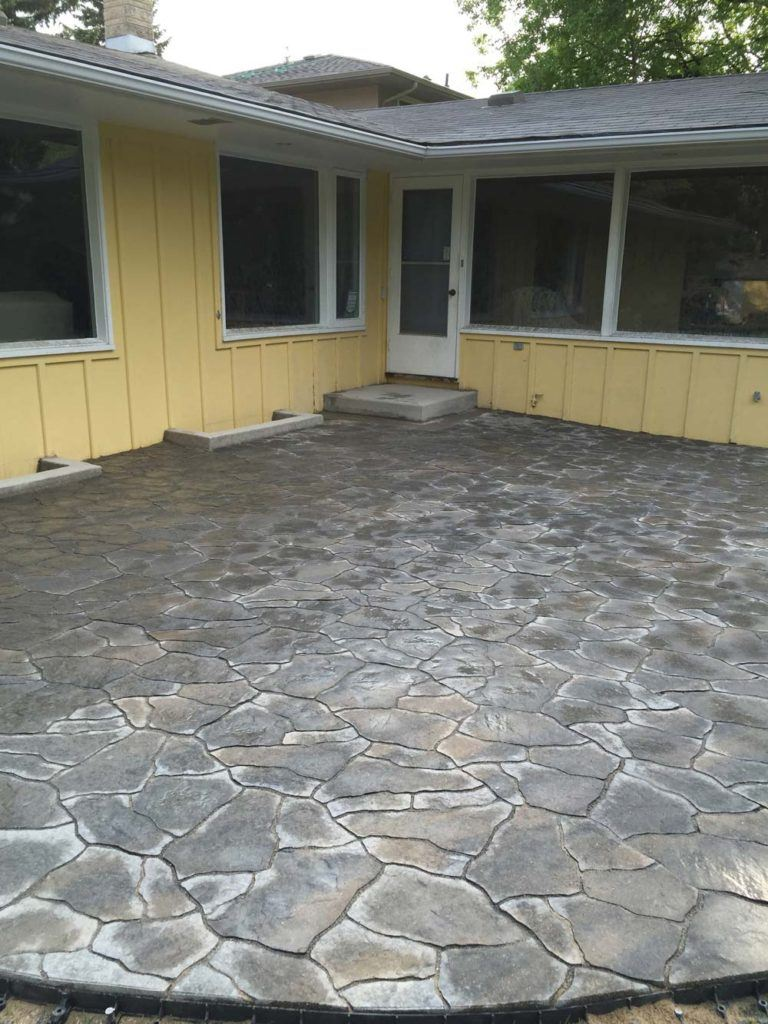 a large flagstone interlock backyard patio outside of a one storey yellow home