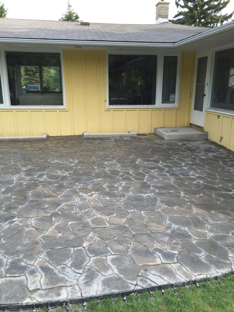 a large flagstone interlock backyard patio