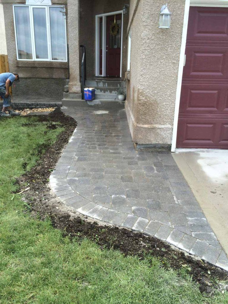 beautiful front entrance to a home with a stone interlock pathway