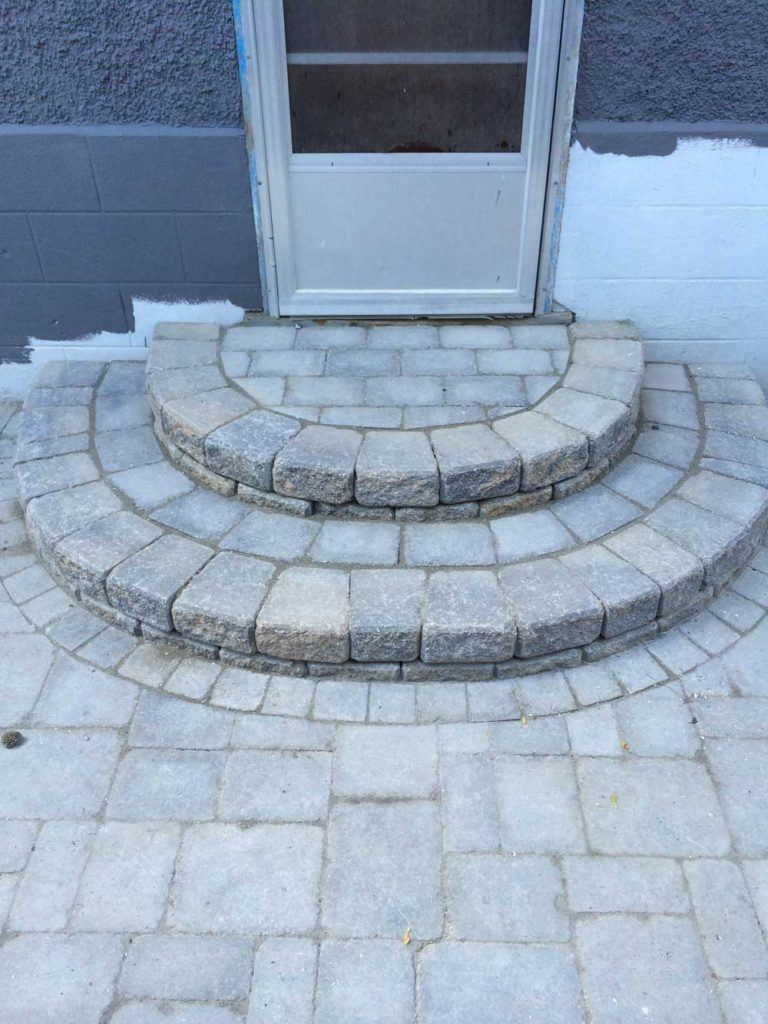 two semi-circle stone steps leading up to a back door