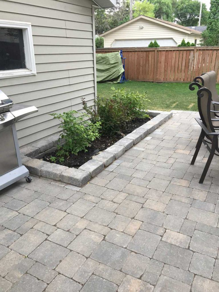 Custom interlock for The Oasis backyard with stone interlock patio and garden