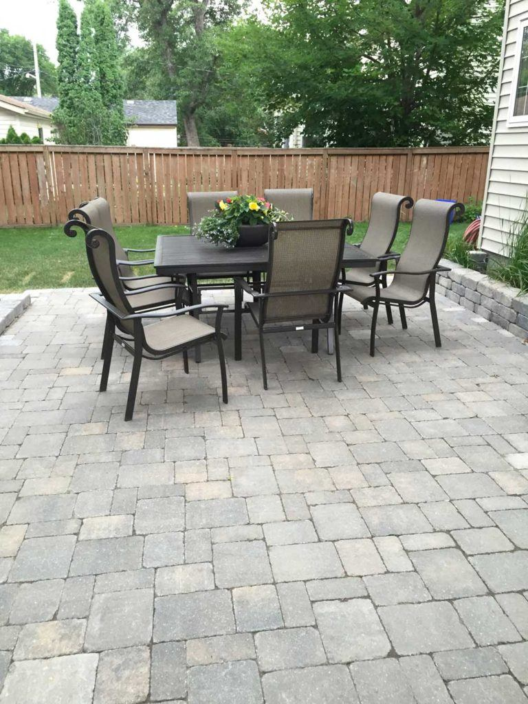 Custom interlock for The Oasis backyard with a large stone interlock patio and table set