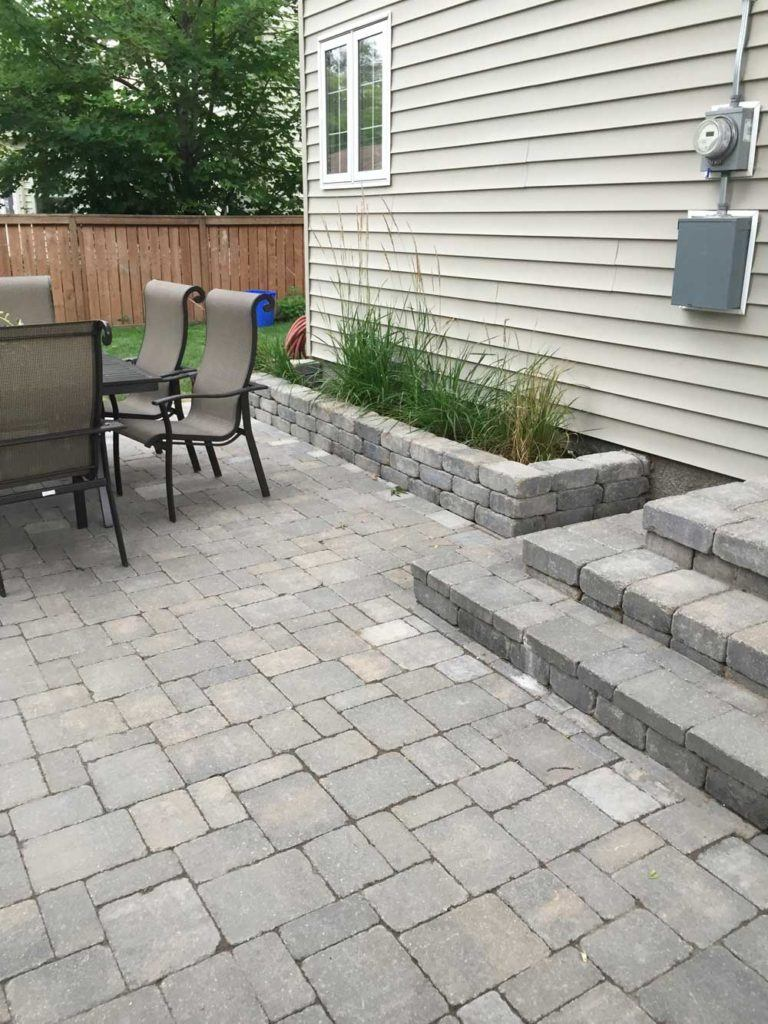 Custom interlock for The Oasis backyard with stone interlock patio and stone garden planters