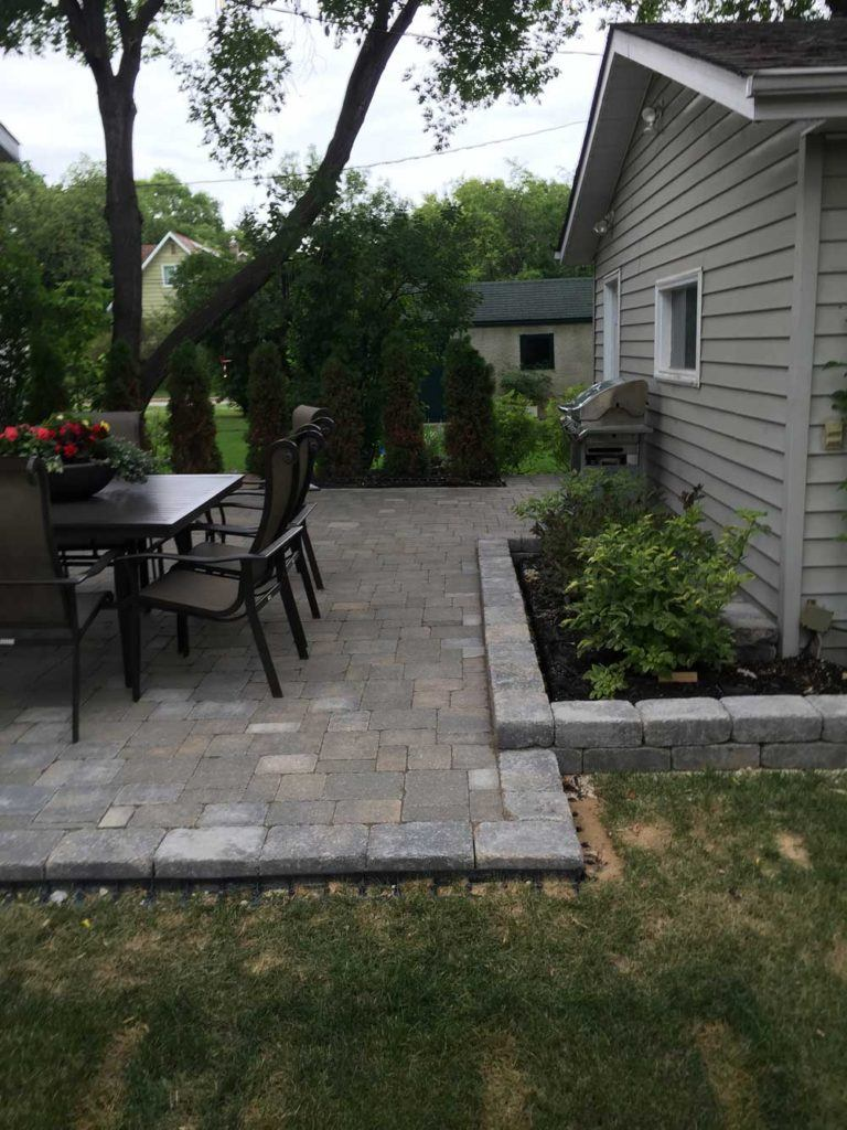 Custom interlock for The Oasis backyard with a large stone patio, bbq, and table set