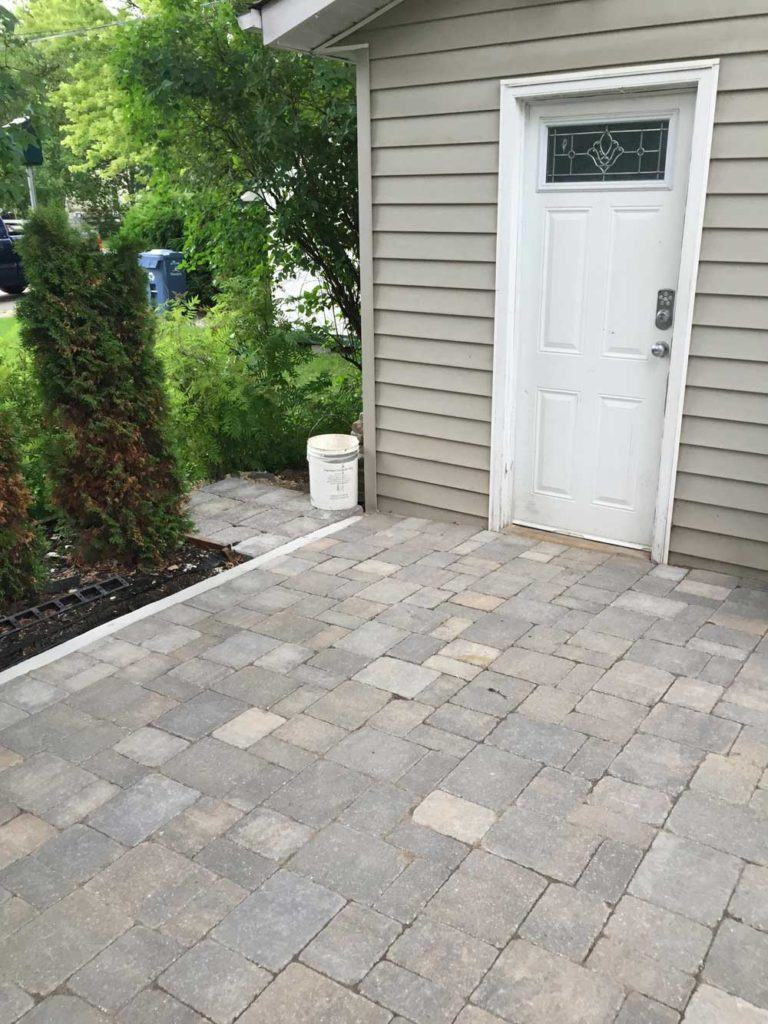 Custom interlock for The Oasis backyard with a stone pathway leading to the shed