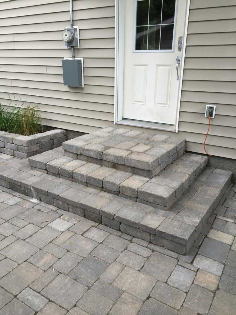 Custom interlock for The Oasis backyard with stone interlock steps leading to the back door
