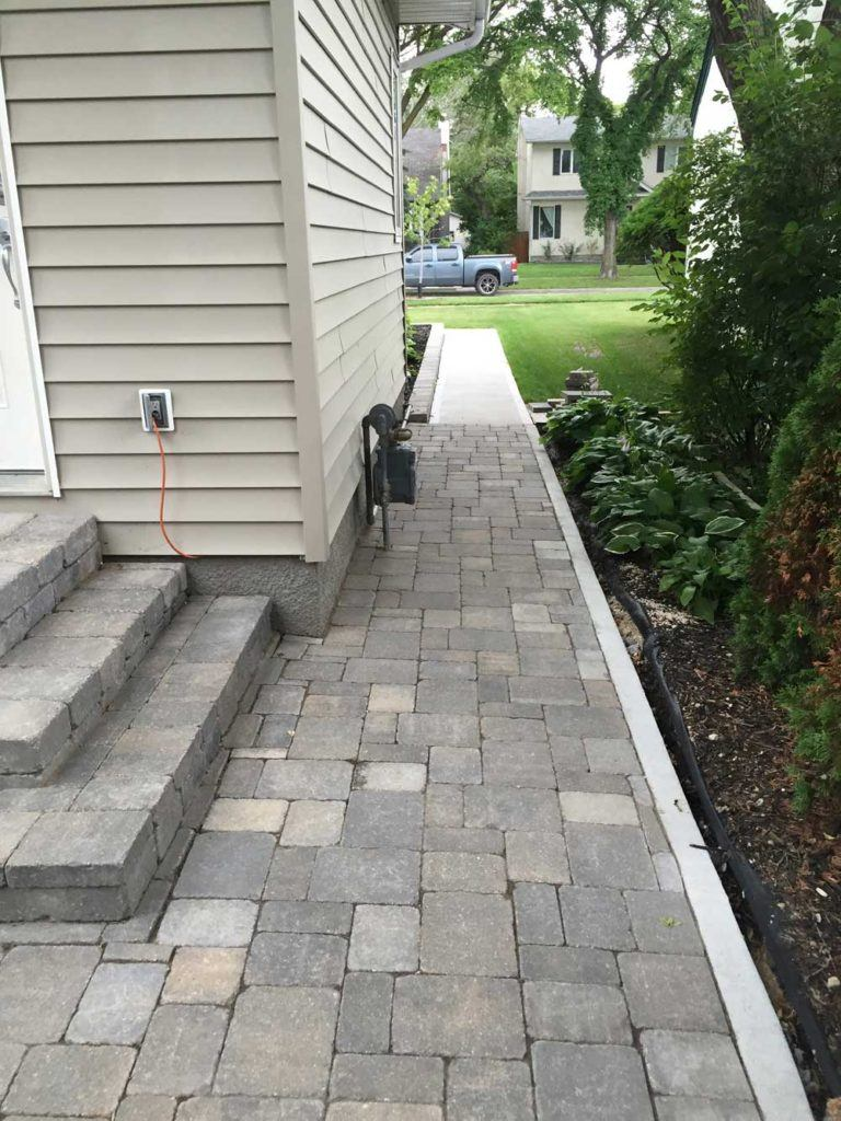 Custom interlock for The Oasis backyard with stone interlock pathway leading to the front yard