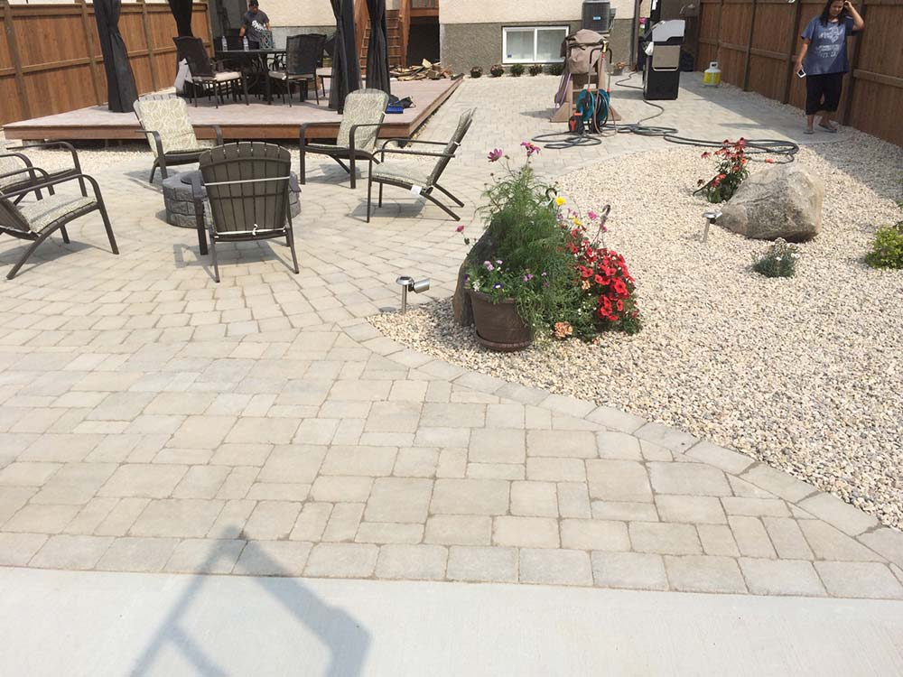 custom interlock stone backyard patio with gravel rock garden