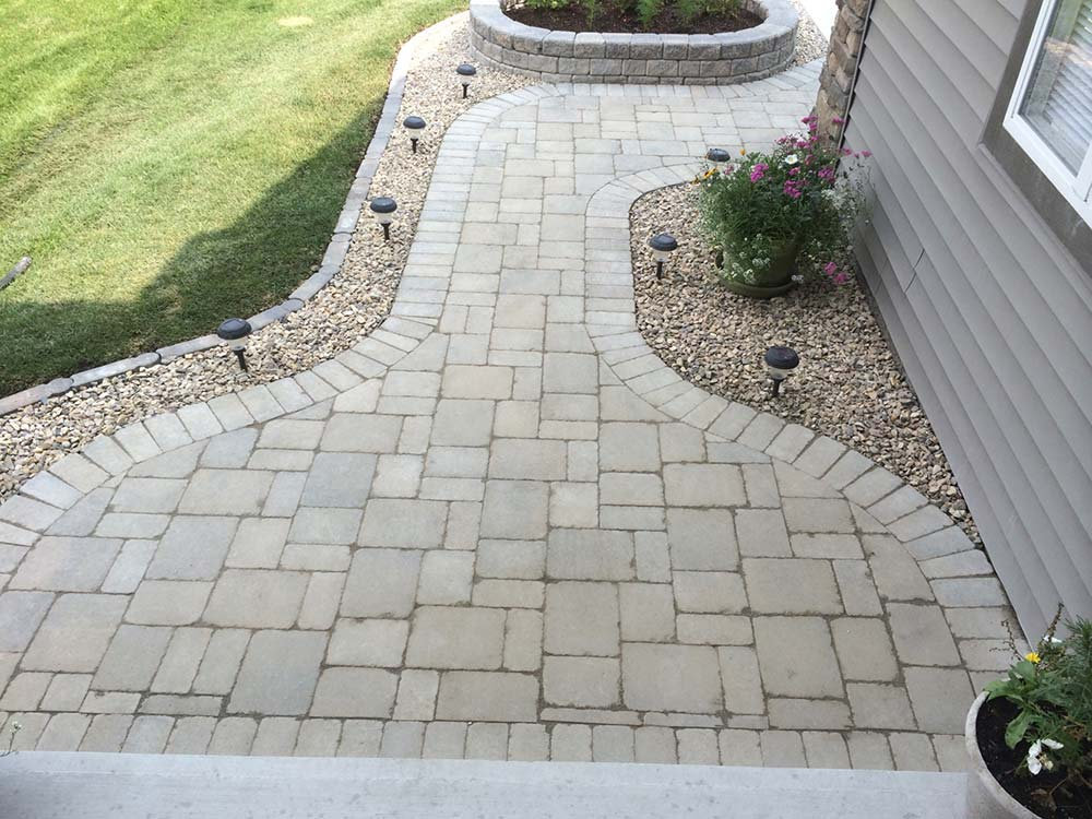 gray concrete interlock pathway with gravel gutters in a backyard lawn