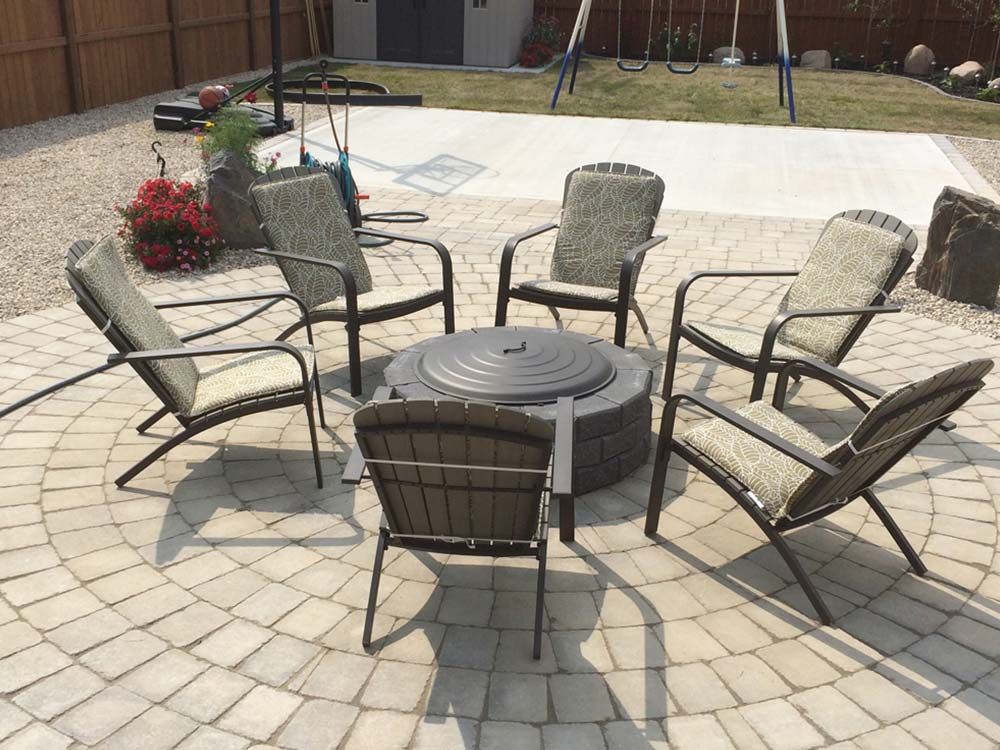 a custom interlock backyard fire pit and circular stone patio
