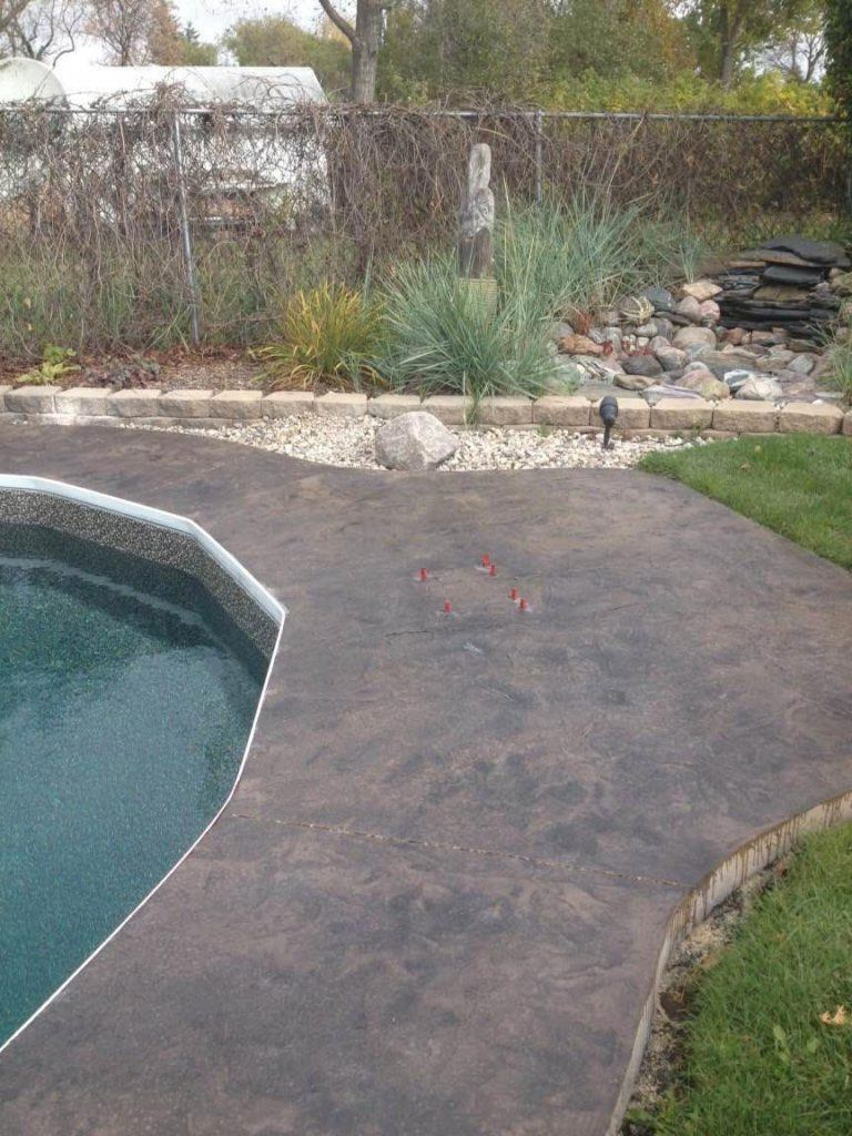 Stamped and coloured concrete surrounding backyard pool