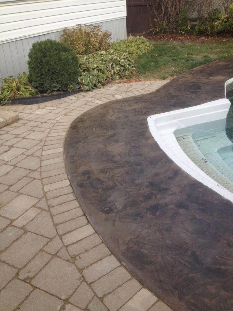Stamped and coloured concrete surrounding in-ground pool