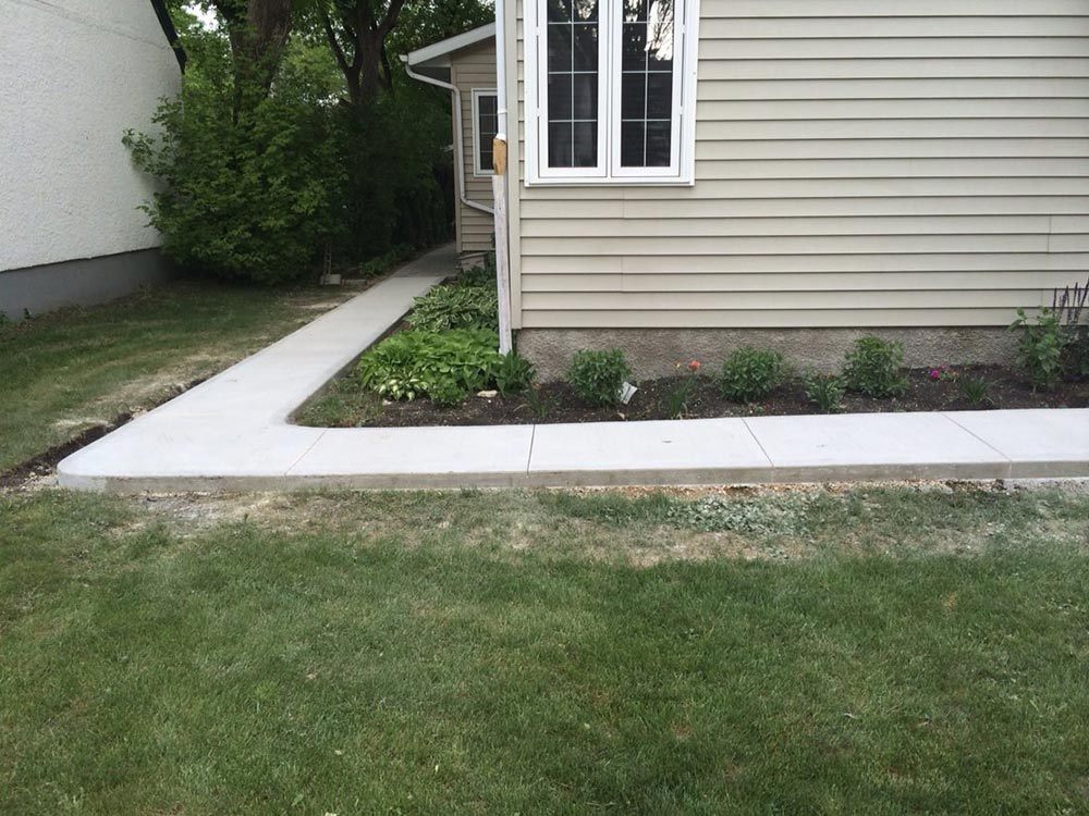 High-quality concrete walkway leading around the corner of a residential home