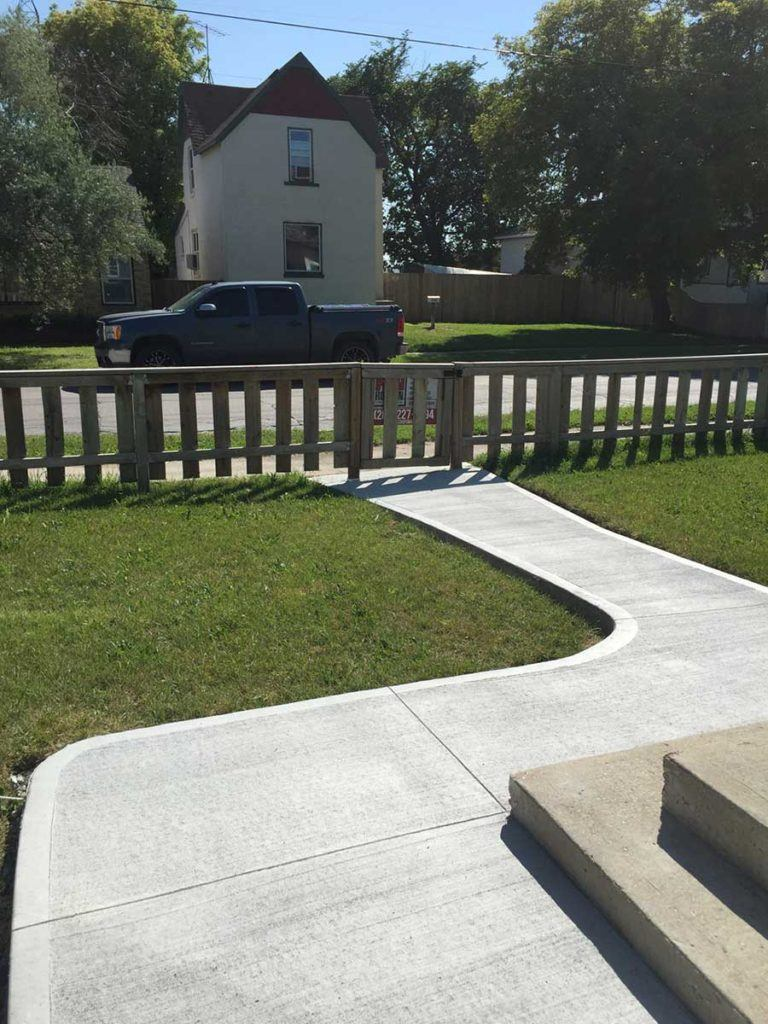 a clean new expertly built concrete path leading from the road to the front of a house