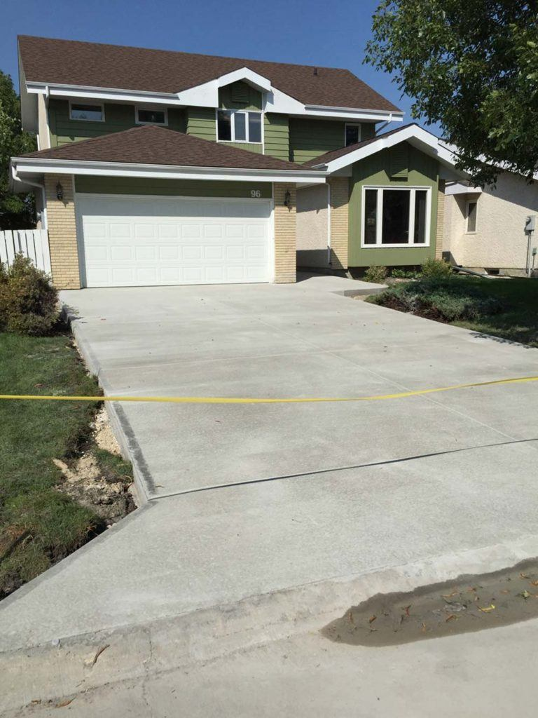 a expert built new concrete driveway in front of a residential home