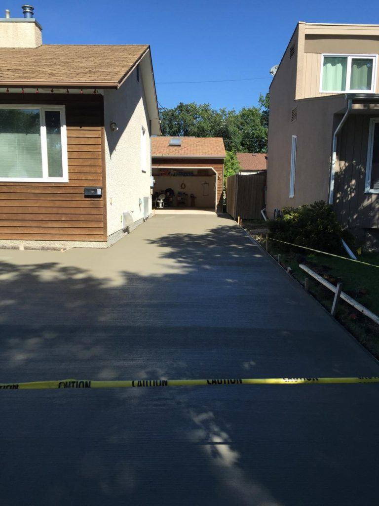 a new concrete driveway outside of a cedar shingled and stucco walled residential home