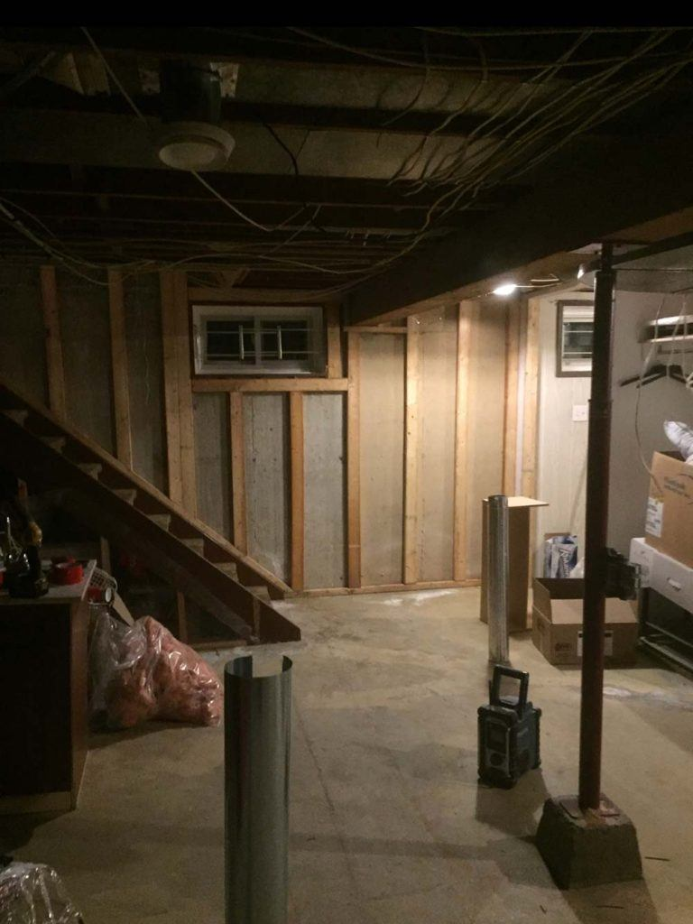 a home basement during a renovation stripped down to concrete and wall studs