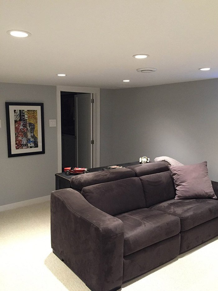 Newly complete basement rec-room renovation with pot lights on the ceiling