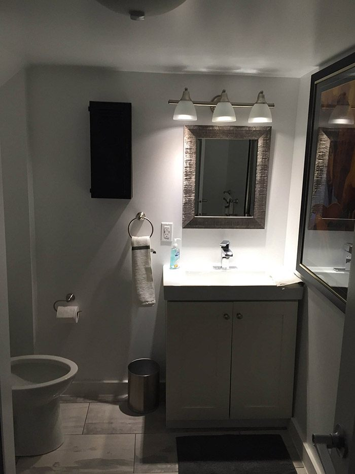 Newly complete basement bathroom renovation with a well lit vanity
