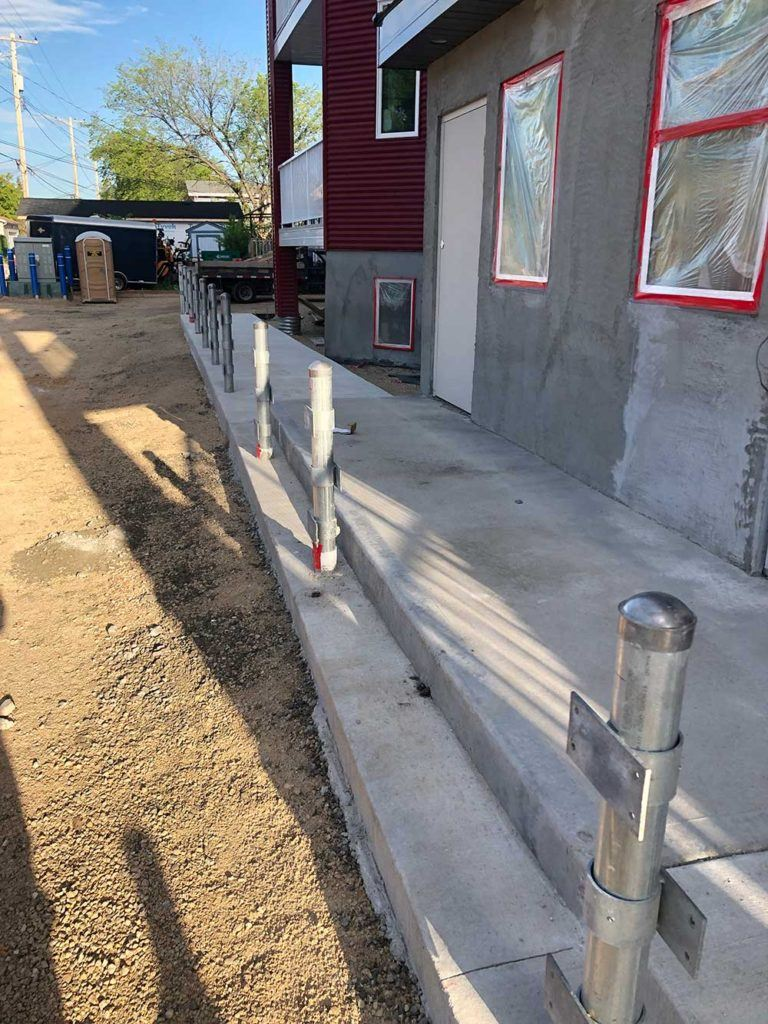 a newly poured concrete walkway in front of a in-progress townhouse development