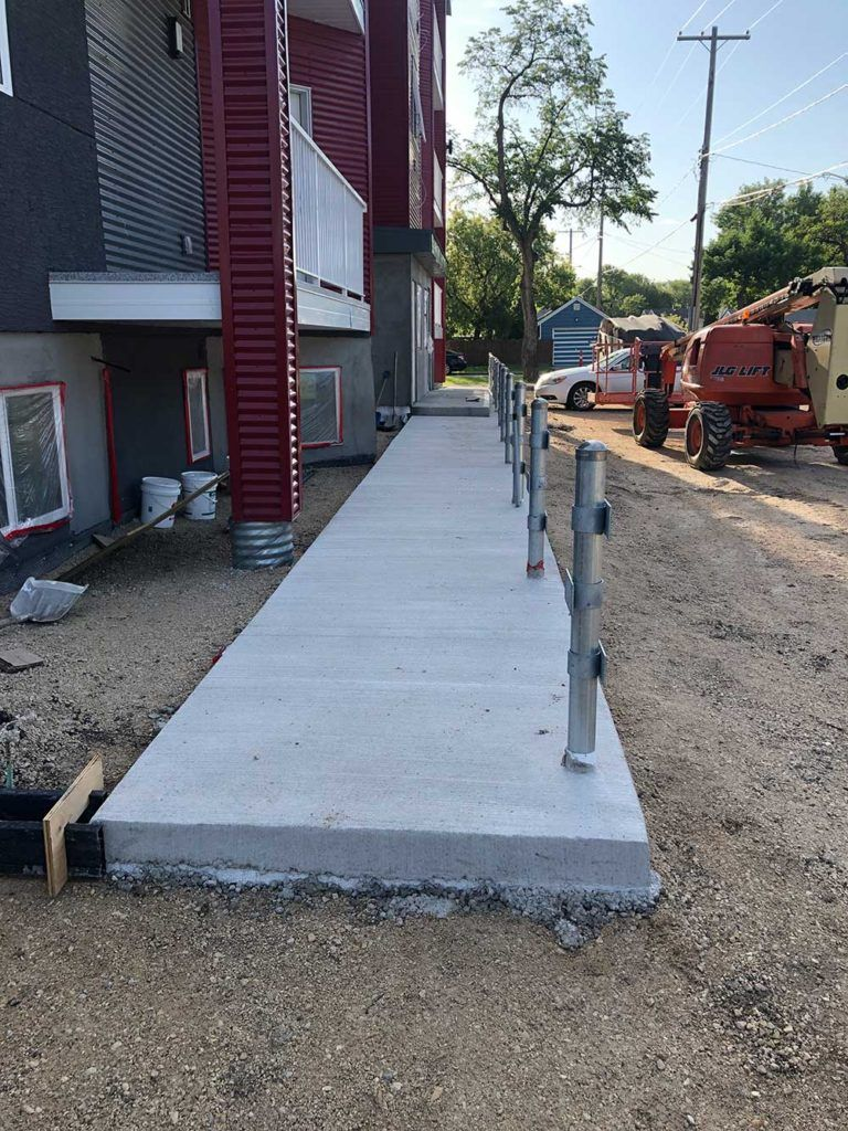 a freshly poured concrete walkway in front of a new townhouse development
