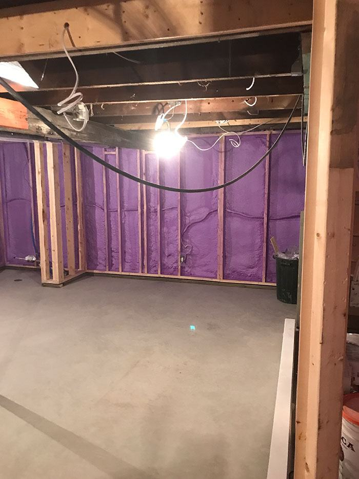 a basement renovation in progress with a new concrete floor and insulated walls