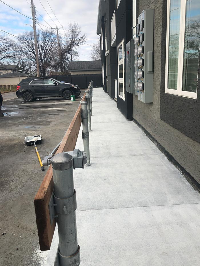 a new concrete walkway beside a small parking lot