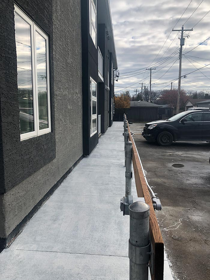 a new concrete walkway beside a small parking lot outside of a small office building