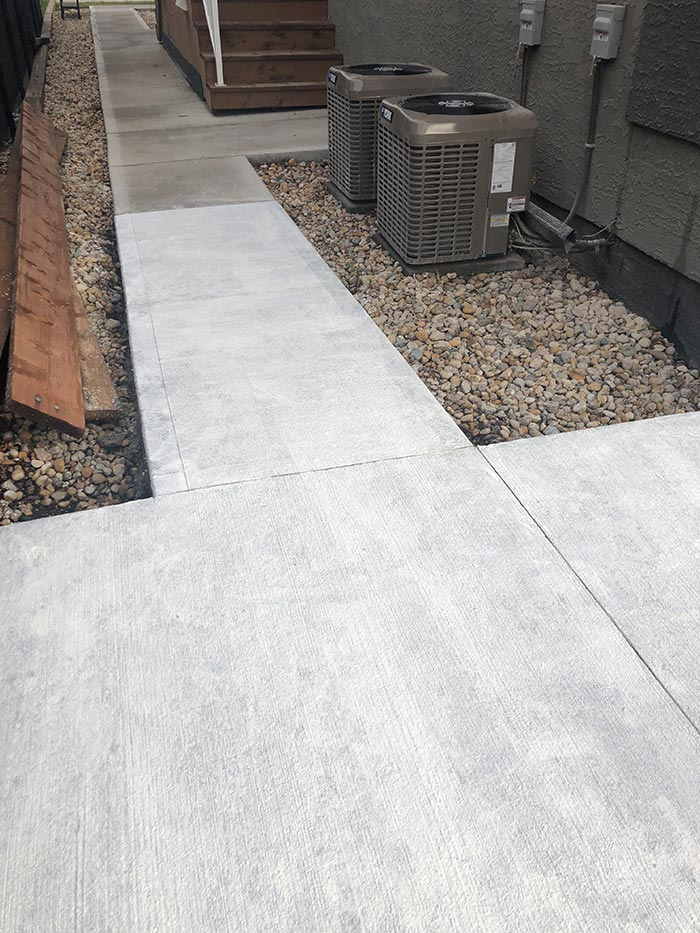 a new concrete walkway surrounded by smooth gravel