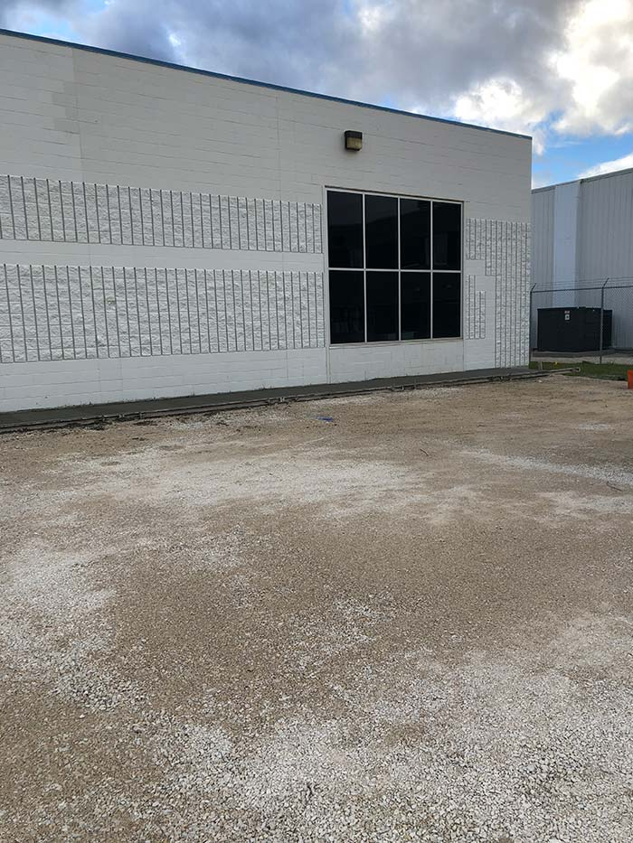 a concrete parking lot in progress behind a commercial building
