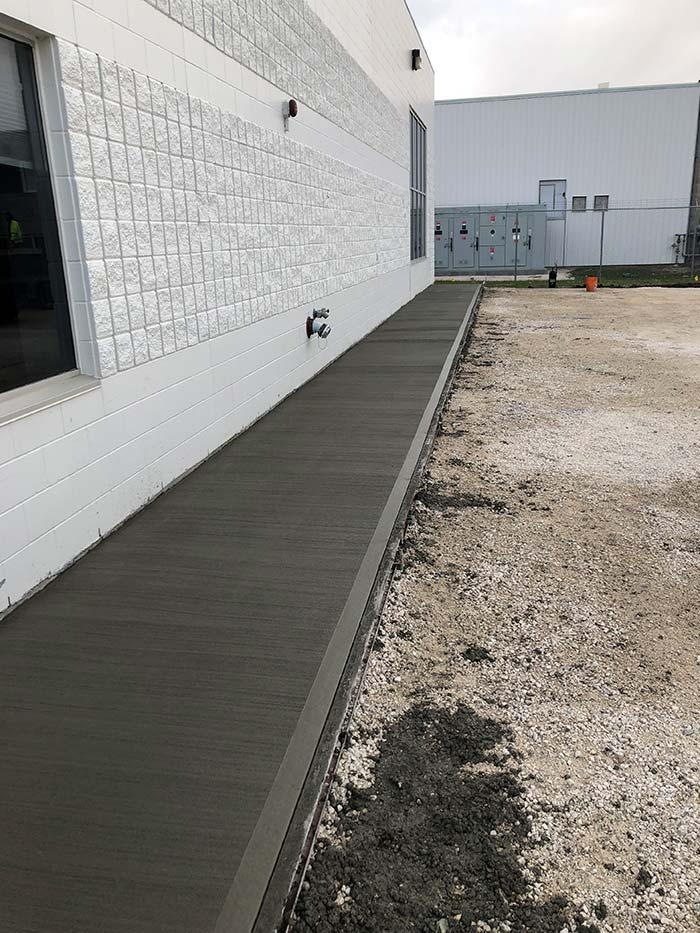new concrete walkway outside of a commercial industrial building