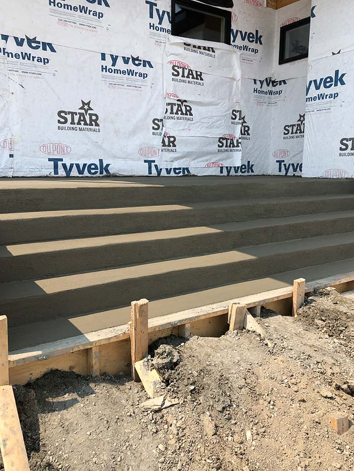 a long set of concrete steps being poured outside of a new building in progress