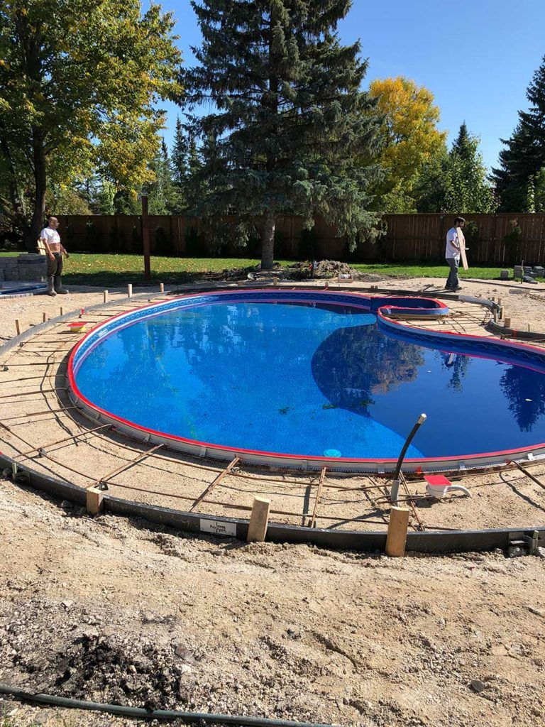 an in-ground pool with a grid of rebar around it where the concrete pool deck will be