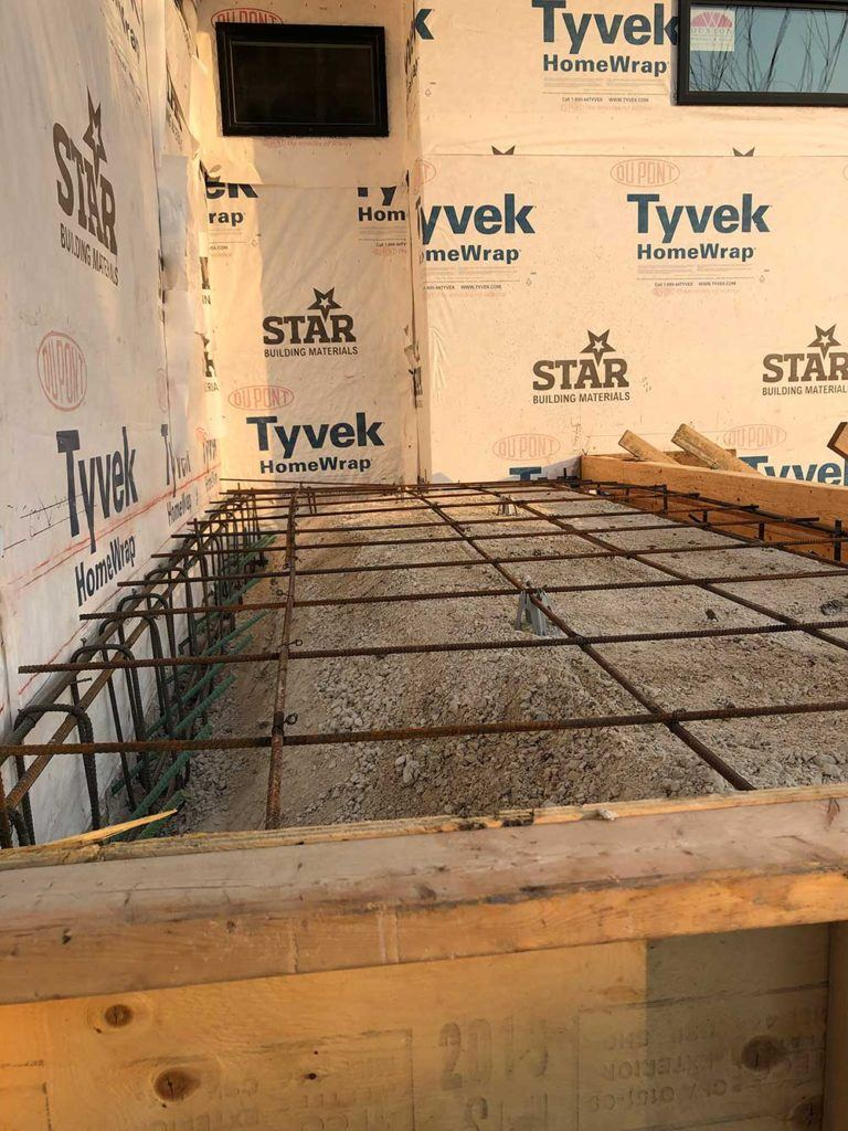 a grid of rebar inside of a concrete molding that will be poured outside of a new house