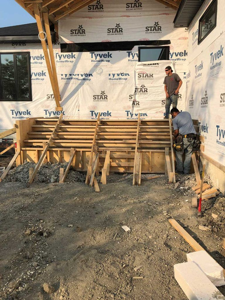 the wooden moldings for a concrete stair set in front of a new-build house in progress