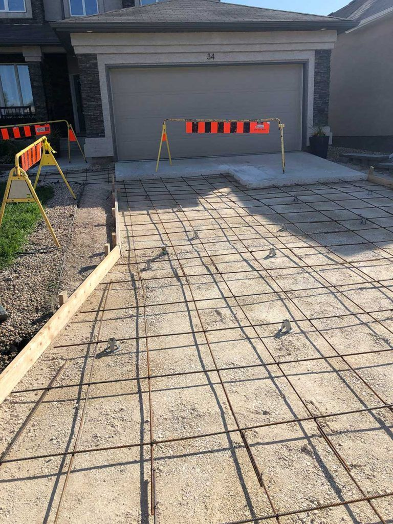 a concrete driveway before the concrete is poured with a grid of rebar for reinforcement