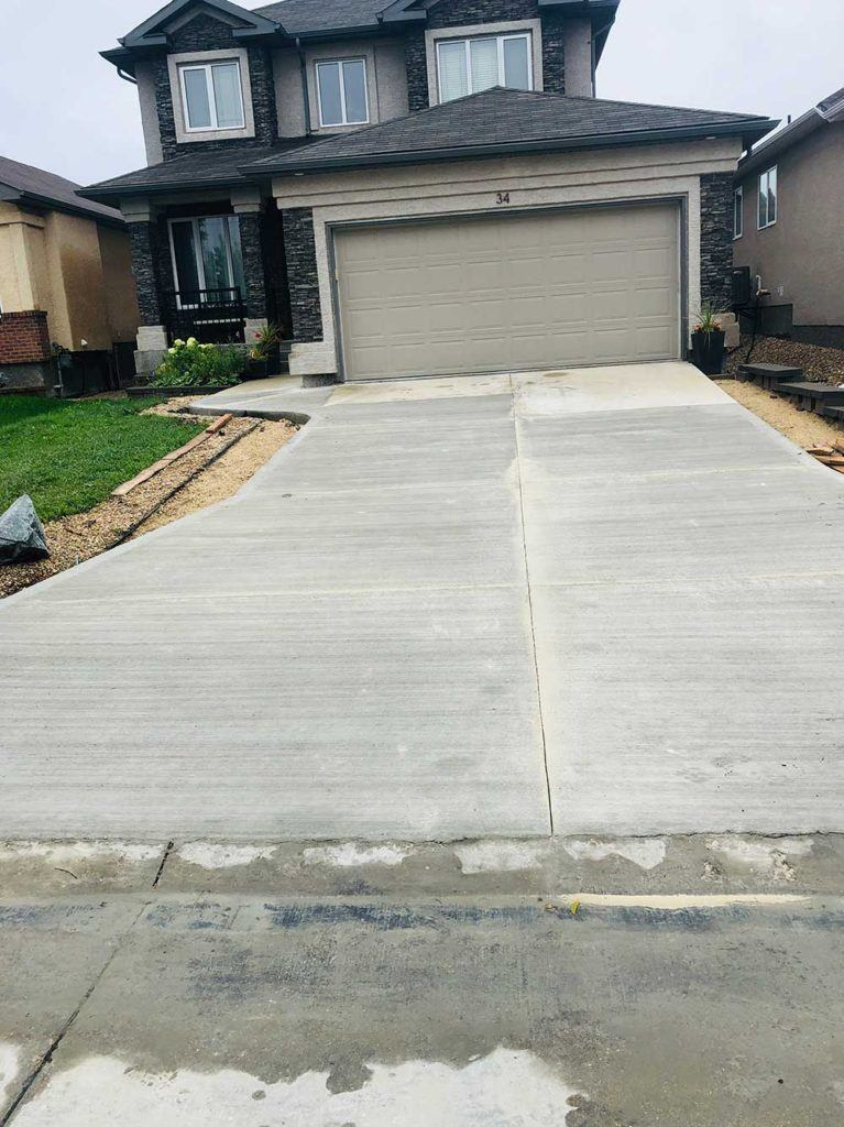 a new concrete driveway leading up to a garage door