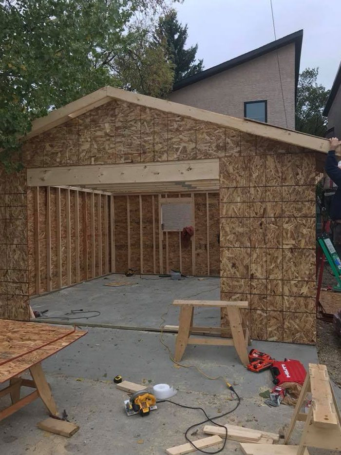a new garage building in progress with plywood walls