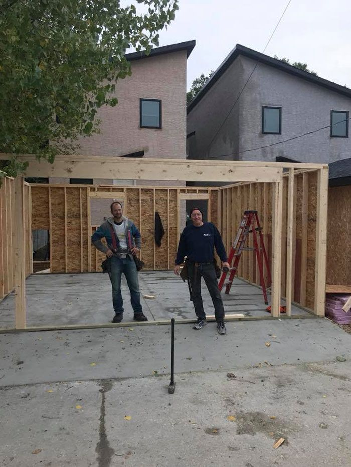 two workers standing outside of a new garage they are building