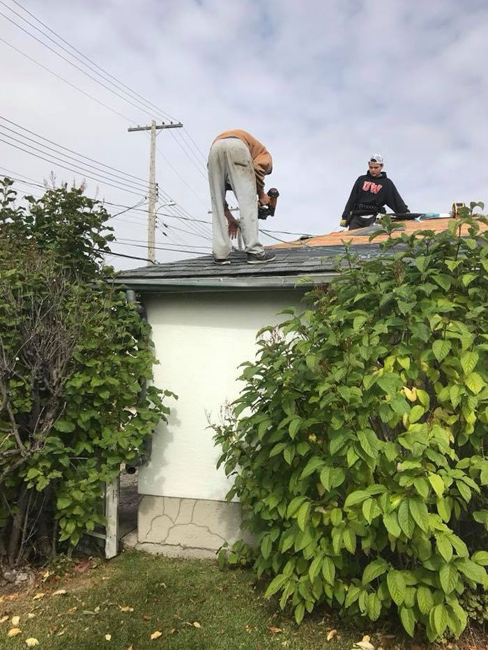 two workers re-shingling a roof on a sunny day