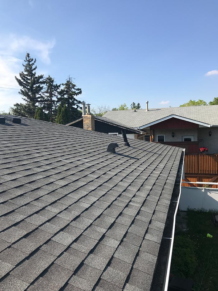 a newly shingled residential home roof on a sunny day